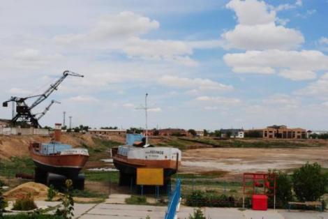 Wybrzeże Aralska (Kazachstan), kutry rybackie i fabryki w oddali. Tylko gdzie jest morze?