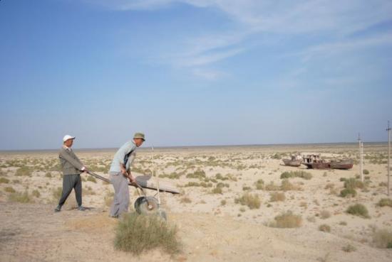 Robotnicy na tle kutrów i dna Morza Aralskiego - Moynaq (Uzbekistan)